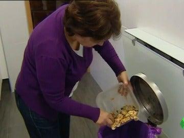 Una mujer tira a la basura algunos restos de comida