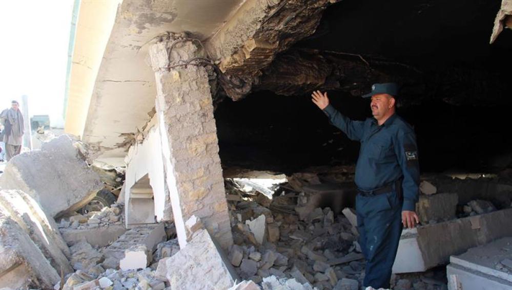 Un oficial de seguridad inspecciona los daños en el escenario de un atentado suicida en Afganistán