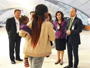 Personal del aeropuerto hablan con miembros de la familia zimbabuense que ha permanecido tres meses en el Aeropuerto Internacional Suvarnabhumi en la provincia de Samut Prakan, a las afueras de Bangkok,