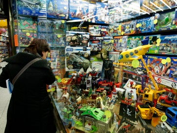 Una mujer contempla los artículos expuestos en el escaparate de una juguetería