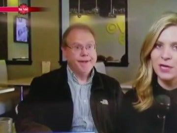 Un señor detrás de una reportera