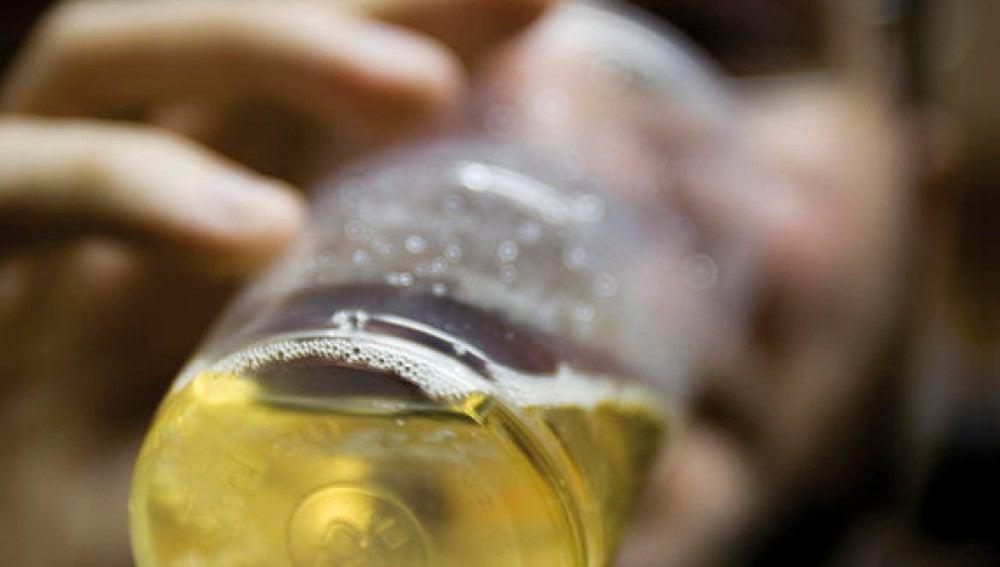 Un joven bebe una bebida alcohólica