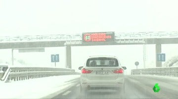 Un coche circula por una carretera cubierta de nieve