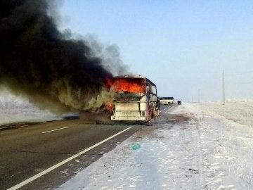 Una columna de humo se eleva desde un autobús por una carretera en Kazajistán