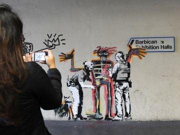 Ciudadanos toman fotografías de una obra del artista Banksy en Londres (Reino Unido)