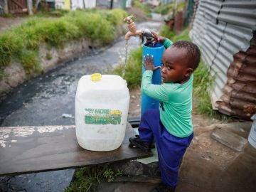 Un niño llenando una garrafa de agua en Ciudad del Cabo
