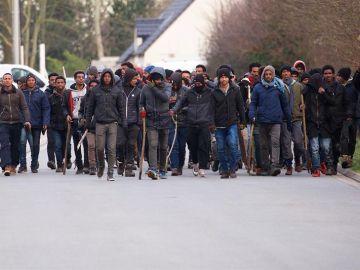 Un grupo de inmigrantes carga palos y piedras durante un enfrentamiento cerca del puerto de Calais