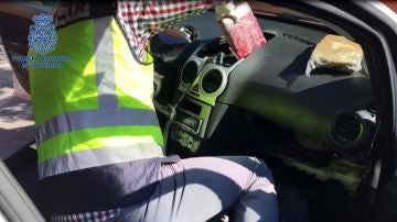 Un agente revisa el salpicadero de un coche en busca de droga