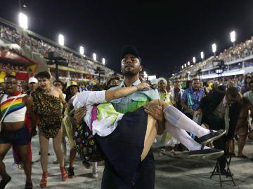 Representación de la violencia en Rio de Janeiro con un policía cargando una estudiante tiroteada