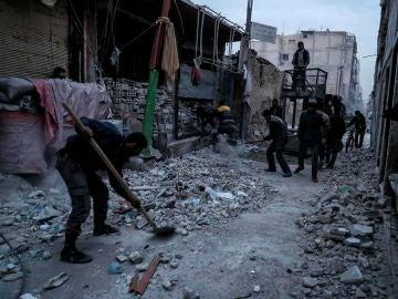 Un hombre quita los escombros tras un bombardeo cerca de Damasco