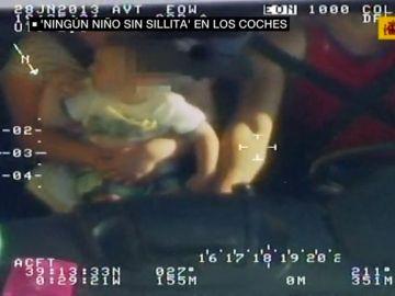 Niño sin sillita en un coche