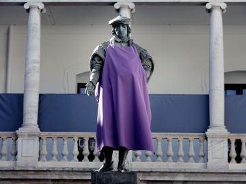 Una estatua con un delantal morado en apoyo a la huelga del 8M