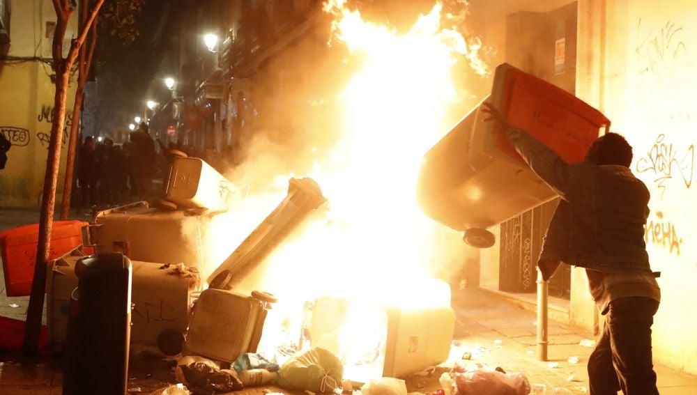 Contenedores incendiados en la calle Mesón de Paredes con la calle del Oso