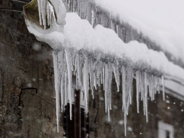 Carámbanos de hielo cuelgan del tejado de una casa de la localidad lucense de O Cebreiro