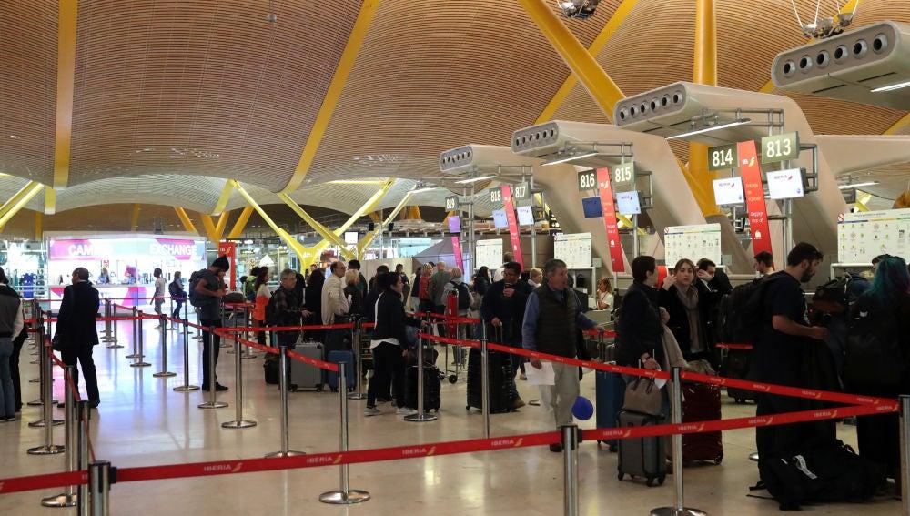 Pasajeros esperan ante los mostradores de facturación del aeropuerto de Barajas de Madrid