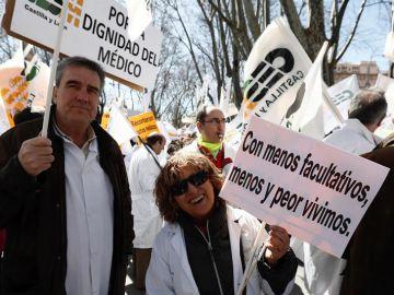 Dos médicos portan pancartas durante la manifestación convocada por el colectivo hoy a las puertas del Ministerio de Sanidad