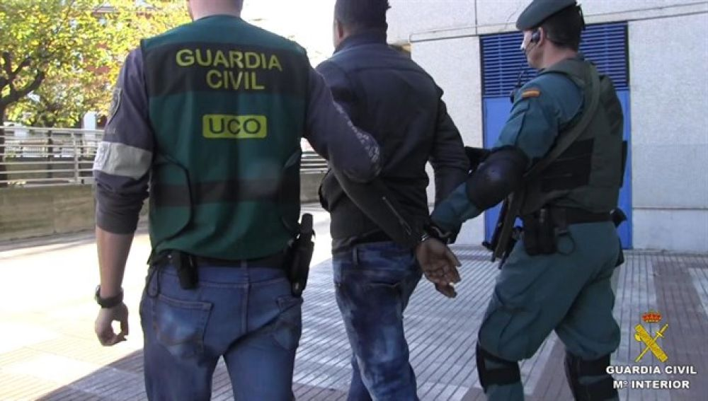 Agentes de la Guardia Civil con uno de los detenidos