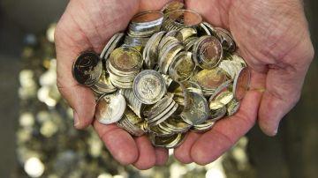 Un hombre sostiene varias monedas de euro