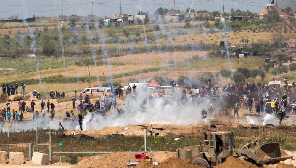 Palestinos huyen de las bombas de gas lacrimógeno lanzadas por tropas israelíes