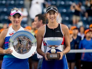 Garbiñe Muguruza sostiene su trofeo de campeona junto a Babos
