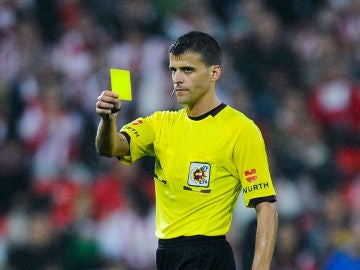 Gil Manzano muestra una tarjeta amarilla durante un partido
