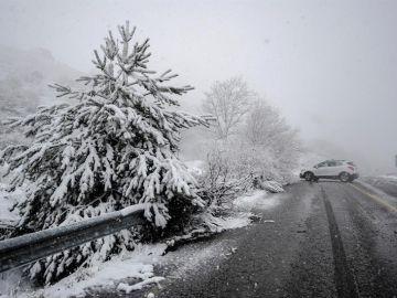 Un coche en una carretera nevada en A Canda (Ourense)