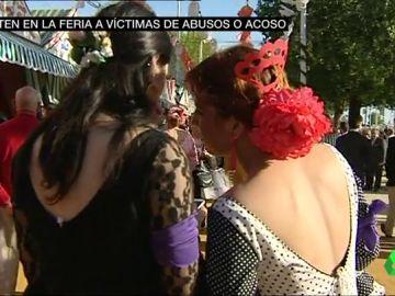 Dos mujeres portan un brazalete morado en la Feria de Abril
