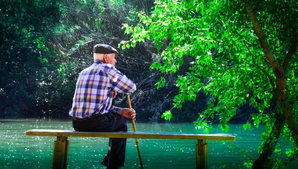 Fotografía de un hombre de avanzada edad, con bastón y boina, sentado en un banco frente a un estanque, en un parque.