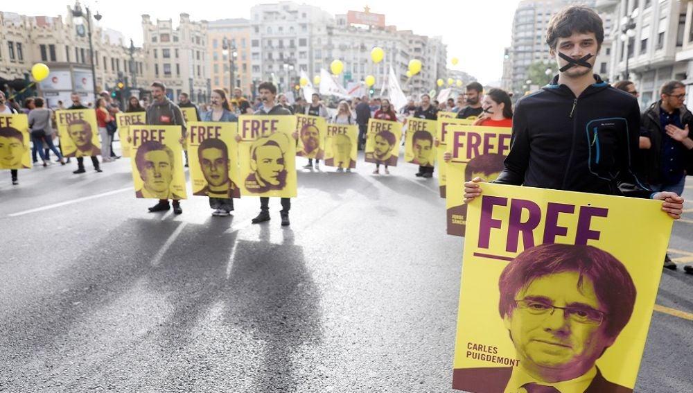 Varios jóvenes con las bocas precintadas llevan pancartas de los diputados catalanes investigados por el porcés