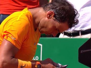 Nadal mira a su móvil tras ganar a Dimitrov