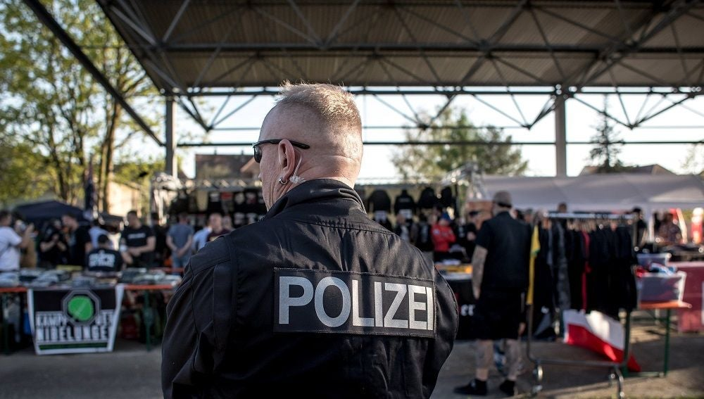 Un policía vigila a los participantes del festival neonazi.