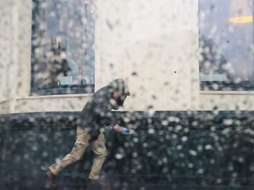 Imagen de archivo de un hombre intentando resguardarse de una tormenta