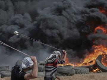 Dos palestinos lanzan piedras en una protesta en Gaza