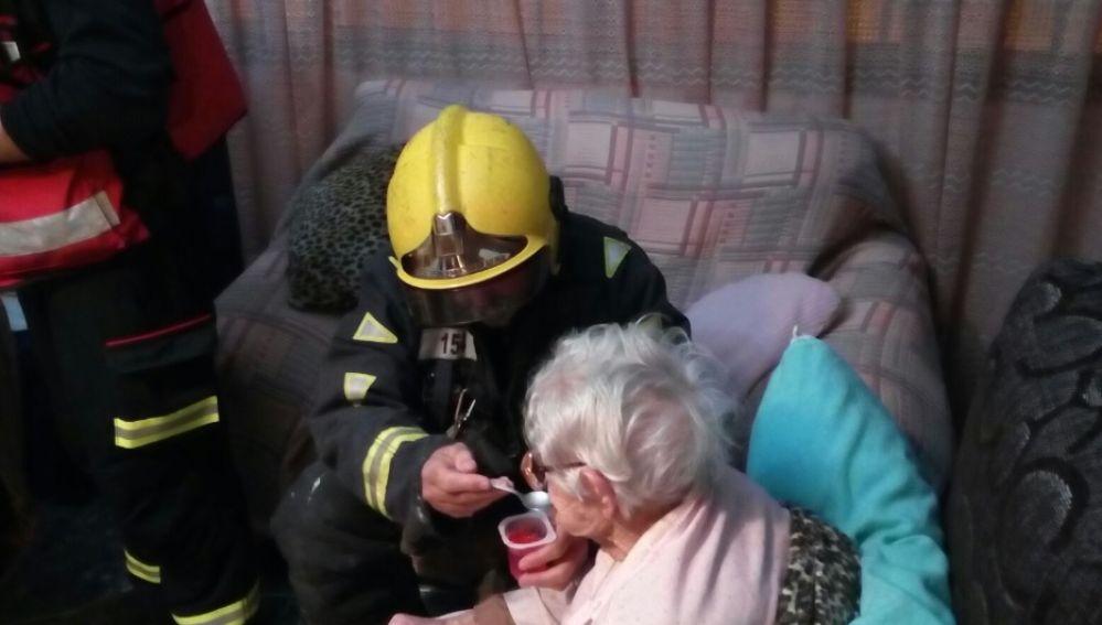 Bomberos dando un yogur a la anciana que pasó varias horas en el suelo