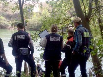 Los agentes y bomberos durante las labores de rescate del cadáver