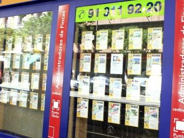 Vista de un escaparate de una inmobiliaria en Madrid, con anuncios de pisos en venta (Archivo)