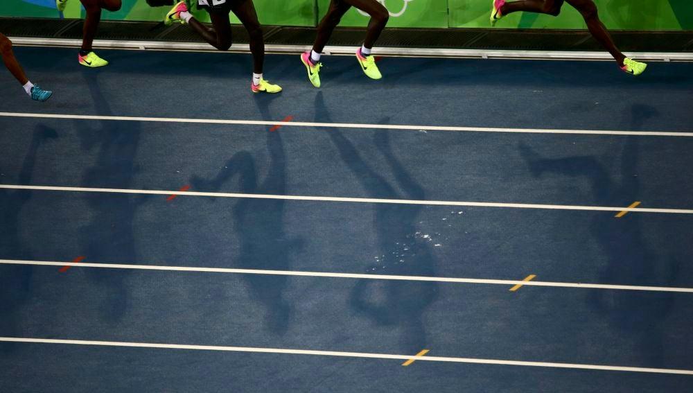 Varios atletas corren en una pista de atletismo