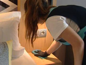 Una limpiadora de  hotel trabaja en una habitación.