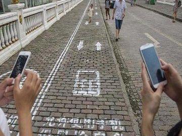 Carril para que circulen personas que utilizan su teléfono móvil