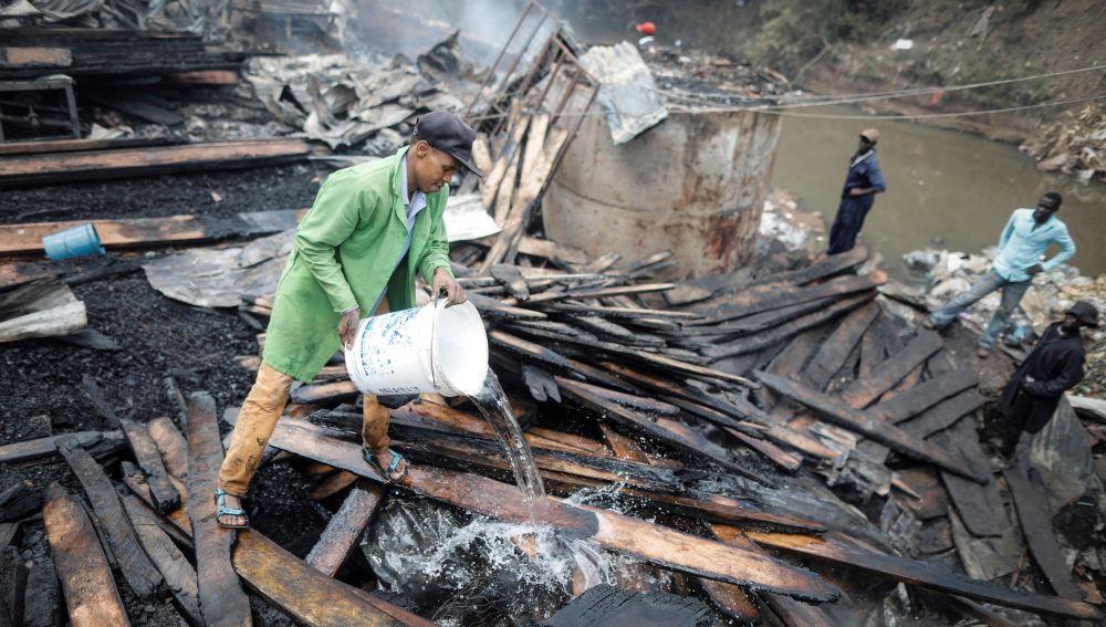 Miembros de los servicios de rescate trabajan entre los escombros tras un incendio en el mercado Gikomba en Nairobi