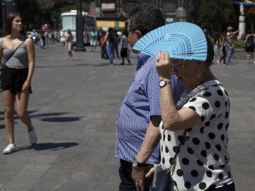 Señora tapándose con el abanico por el calor
