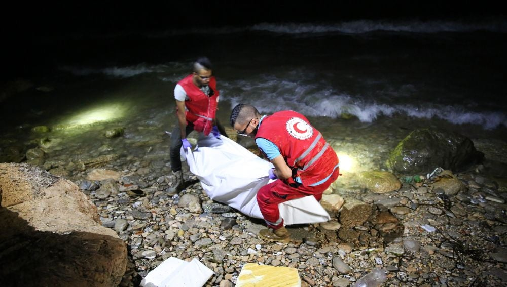 Personal de rescate de la Media Luna Roja Libia transportan el cuerpo de un inmigrante fallecido.