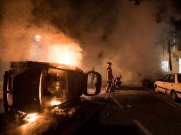 Los bomberos tratan de apagar el fuego de un coche incendiado en el barrio de Malakoff , en Nantes