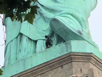 Una mujer escala la estatua de la libertad