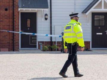 Un policía pasea fuera de la casa de Dawn S. y Charlie R