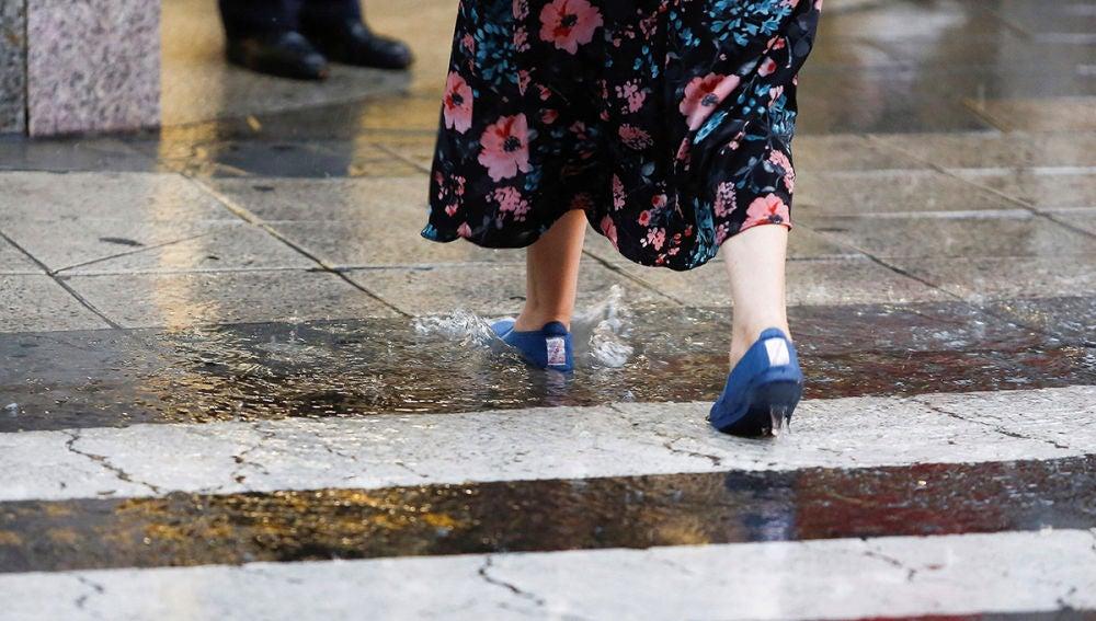 Imagen de una mujer cruzando bajo fuertes lluvias