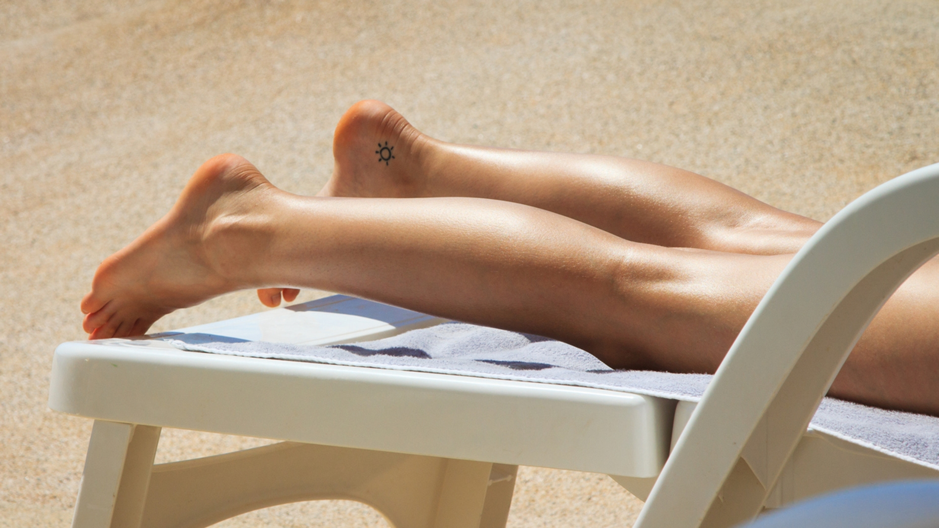 Mujer con tatuaje toma el sol