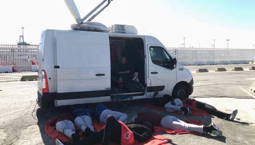 Un grupo de migrantes se resguardan del calor frente a una unidad móvil de laSexta.