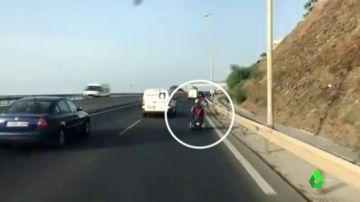 Circula con una silla de ruedas motorizada por una autovía de Málaga