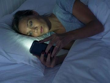 Una mujer mira el móvil antes de dormir